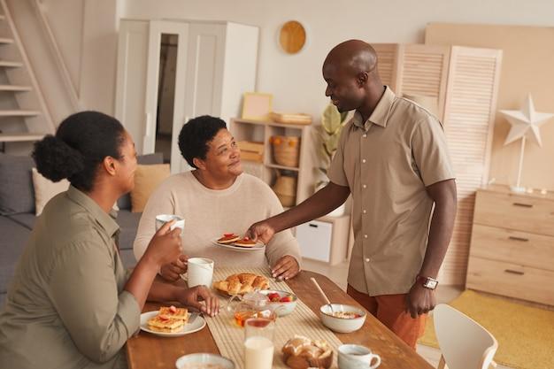 Retrato em tons quentes de uma família afro-americana feliz tomando café da manhã em casa em um interior aconchegante