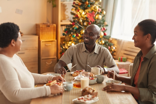 Retrato em tons quentes de uma família afro-americana tomando chá e lanches enquanto celebra o natal em casa