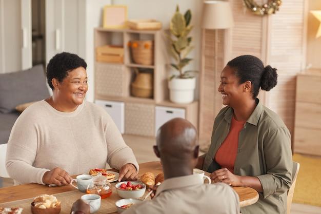 Retrato em tons quentes de uma família afro-americana tomando chá e lanches enquanto toma o café da manhã em casa em um interior aconchegante