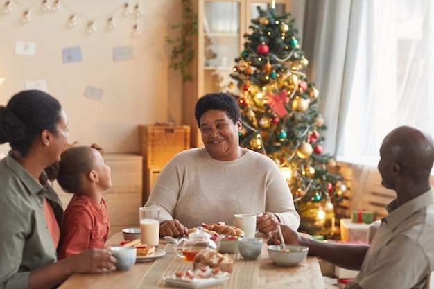 Retrato em tons quentes de uma grande família afro-americana tomando chá e lanches enquanto celebra o natal em casa