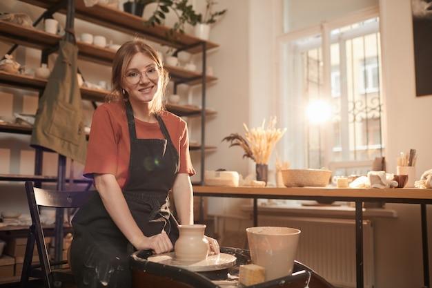 Retrato em tons quentes de uma jovem artesã sorrindo para a câmera enquanto trabalhava na roda de oleiro em uma oficina iluminada pelo sol e apreciava artes e ofícios, copie o espaço