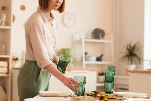 Retrato em tons quentes de uma jovem servindo a mesa no interior da cozinha minimalista