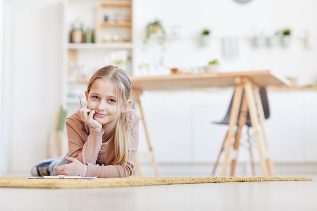 Retrato em tons quentes de uma linda garota loira sorrindo para a câmera e deitada no chão de carpete enquanto desenha ou estuda no interior aconchegante de uma casa, copie o espaço