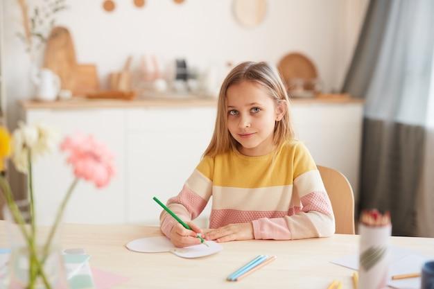 Retrato em tons quentes de uma linda garotinha sorrindo enquanto tira fotos ou faz a lição de casa enquanto está sentada à mesa no interior da casa, copie o espaço
