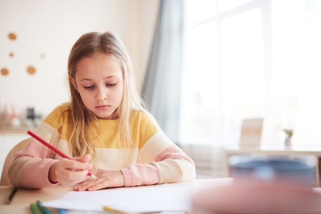 Retrato em tons quentes de uma linda garotinha tirando fotos ou fazendo lição de casa enquanto está sentado à mesa no interior da casa, copie o espaço