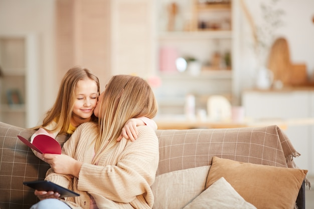 Retrato em tons quentes de uma linda menina dando um cartão de natal para uma mãe feliz no dia das mães ou dia dos namorados, copie o espaço