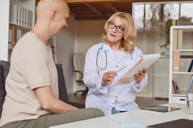 Retrato em tons quentes de uma médica alegre segurando uma prancheta e conversando com um paciente careca durante uma consulta sobre alopecia e recuperação de câncer.