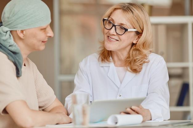 Retrato em tons quentes de uma médica sorridente conversando com uma mulher careca e mostrando dados em um tablet digital durante uma consulta sobre alopecia e recuperação do câncer, copie o espaço