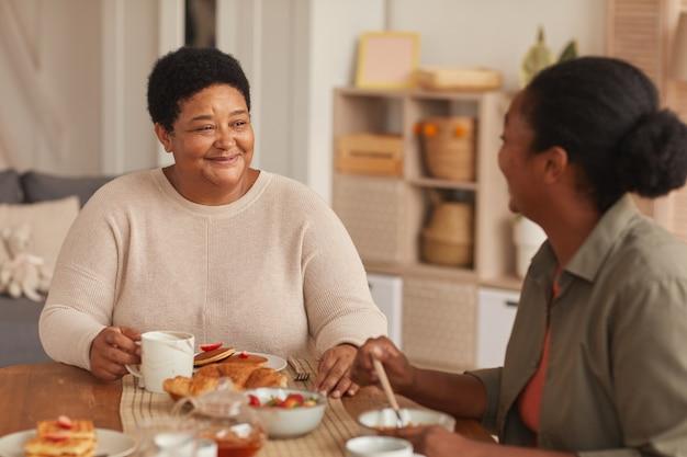 Retrato em tons quentes de uma mulher afro-americana feliz sentada à mesa de jantar com a filha, enquanto tomam o café da manhã juntos em casa