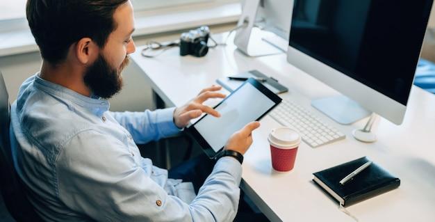Retrato em vista superior de um homem barbudo usando um tablet enquanto bebe um café em seu escritório