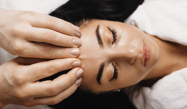 Retrato em vista superior de uma mulher caucasiana deitada e tendo uma sessão de massagem facial no spa