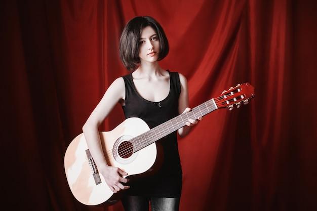 Retrato emocional da menina morena com cabelo preto liso curto, com uma maquiagem natural sobre fundo vermelho. uma mulher em uma camiseta preta com um violão nas mãos