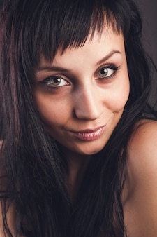 Retrato emocional de baixa chave de uma linda garota sorridente. foto de estúdio