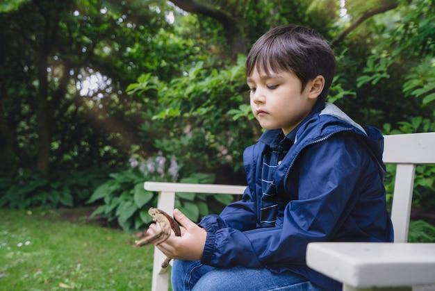 Retrato emocional de criança solitária sentada no banco do jardim