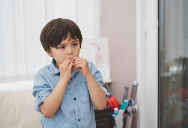 Retrato emocional de criança sozinho com rosto pensativo, jovem rapaz colocando o dedo na boca.