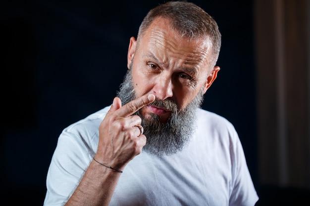 Retrato emocional de um homem adulto de cabelos grisalhos com barba em uma camiseta branca