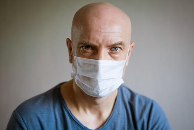 Retrato emocional de um homem careca com uma máscara protetora e uma camiseta azul