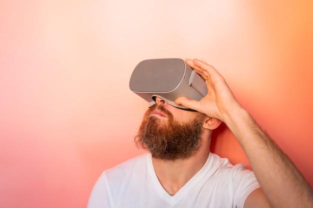 Retrato emocional de um homem com barba usando óculos de realidade virtual no estúdio em um fundo rosa laranja