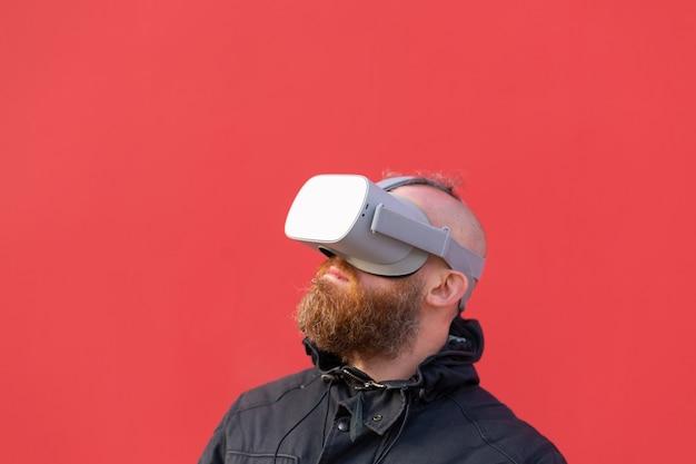 Retrato emocional de um homem na rua usando óculos de realidade contra o fundo de uma parede vermelha