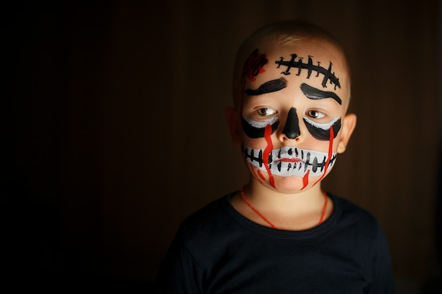 Retrato emocional de um menino com um zumbi assustador no rosto