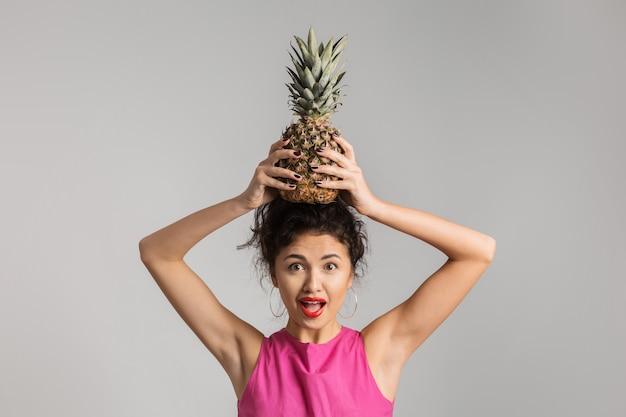 Retrato emocional de uma jovem exótica mulher morena de camisa rosa segurando um abacaxi na cabeça