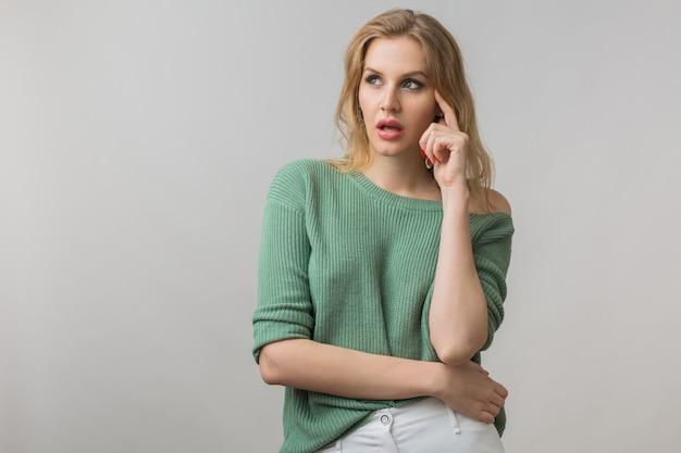 Retrato emocional de uma jovem mulher atraente, pensando, ideia, segurando o dedo na cabeça dela, tendo problemas, frustrada, estilo casual, suéter verde, braços cruzados, isolado, olhando para cima