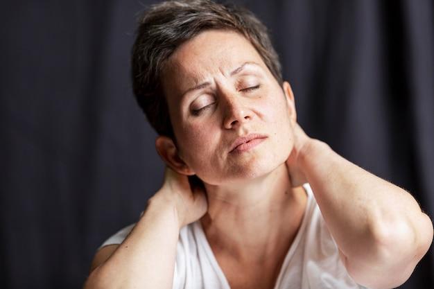 Retrato emocional de uma mulher adulta com cabelo curto e olhos fechados. fundo preto.