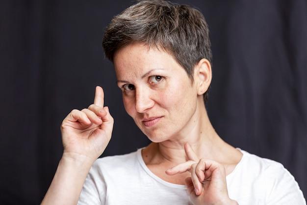 Retrato emocional de uma mulher adulta com cabelo curto. fundo preto.
