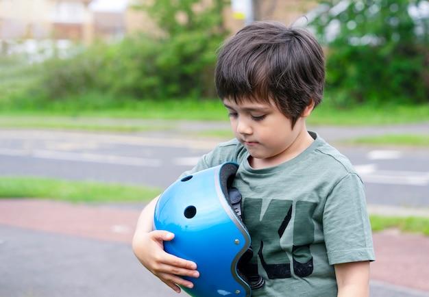 Retrato emocional do garoto garoto com cara triste, segurando o capacete de segurança em pé ao lado da estrada, criança solitária olhando para baixo com o rosto triste, sozinho no caminho