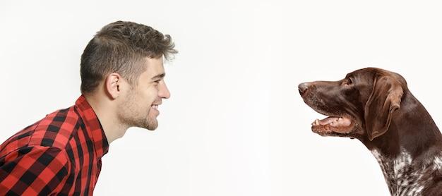 Retrato emocional do homem e seu cachorro, conceito de amizade e cuidado do homem e dos animais. ponteiro de pêlo curto alemão - cachorrinho kurzhaar isolado no fundo branco do estúdio