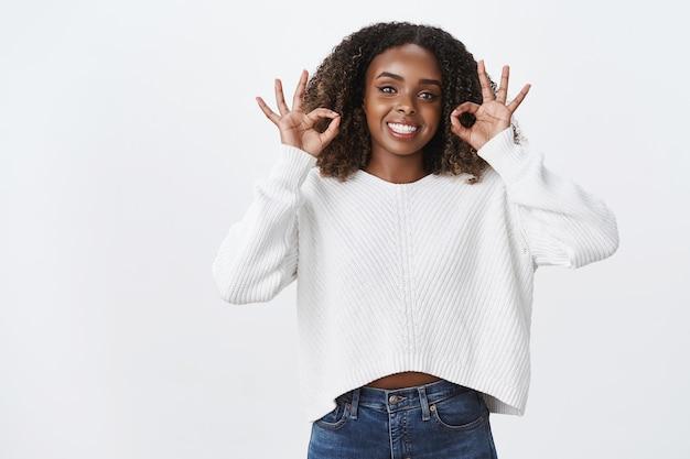 Retrato encantado garantido mulher bonita de pele escura sorridente penteado encaracolado usar suéter mostrar ok concordo, gesto perfeito dar aprovação como conceito