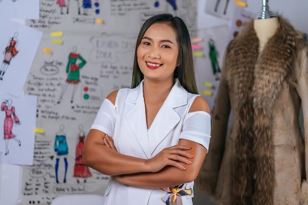 Retrato encantador de estilista asiático ou alfaiate sorrindo feminino feliz em um ateliê moderno