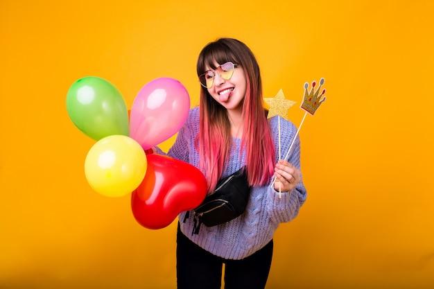 Retrato engraçado brilhante de mulher alegre hippie com cabelo rosa brilhante, vestindo uma camisola confortável, segurando a coroa falsa festa e sorrindo, pronto para a festa, parede amarela.
