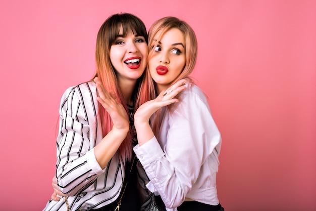 Retrato engraçado de duas garotas felizes e surpresas se divertindo muito juntas e fofocando, com roupas legadas em preto e branco