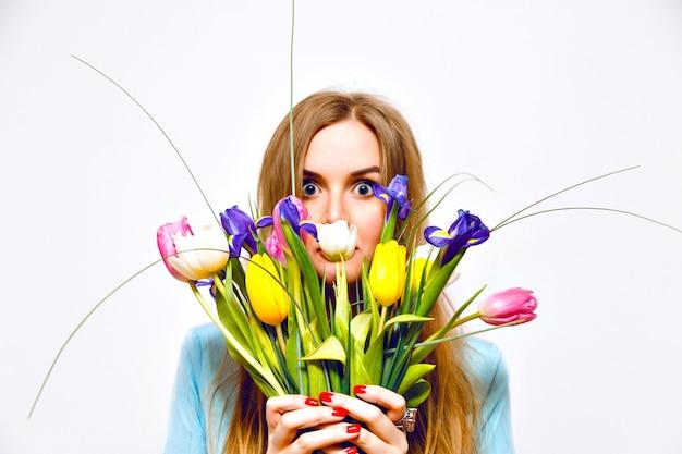 Retrato engraçado de estúdio de mulher loira fechar seu rosto por lindo buquê de tulipas coloridas, tons pastel suaves, vestido vintage, cabelos longos, detalhes de moda. a primavera está chegando