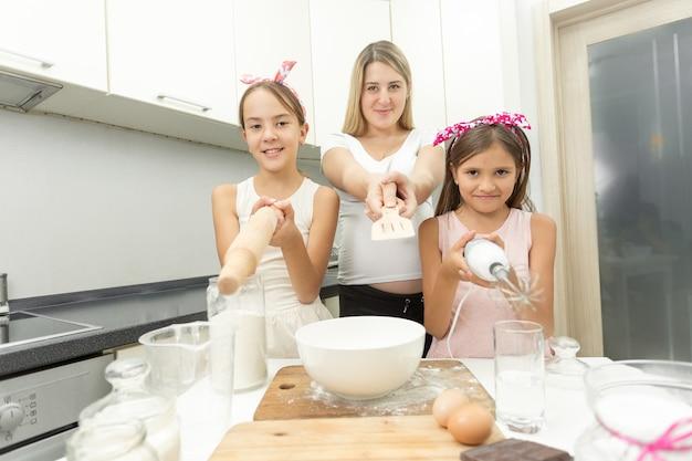 Retrato engraçado de mãe e filha apontando utensílios para a câmera na cozinha
