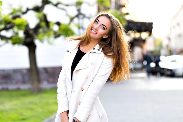 Retrato engraçado de menina loira feliz, fazendo caretas e mostrando a língua na rua, tempo de outono, descanso na cidade.