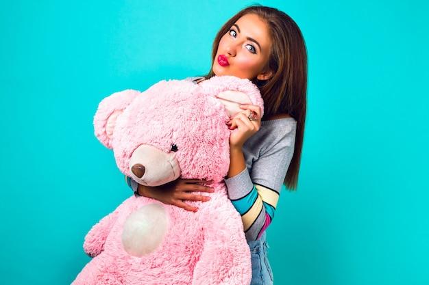 Retrato engraçado de mulher bonita brincando com um grande urso de pelúcia fofo, doces cores pastel. segurando o presente dela e mandando beijo, fazendo careta, feriados, alegria, infância.