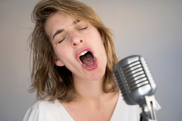 Retrato engraçado de mulher caucasiana, cantando uma música com um microfone de prata vintage.