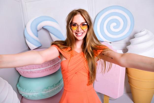Retrato engraçado de mulher loira fazendo selfie, sorrindo e gritando, óculos de sol do coração, vestido da moda de cabelos loiros. cores pastel, vista da doçura do big face, sorvete, macaroons.