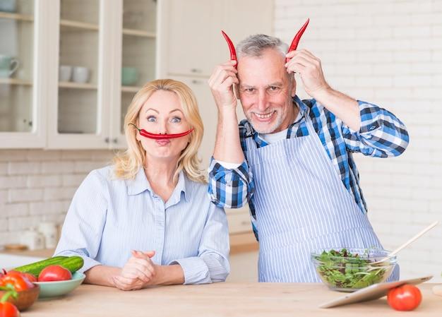Retrato engraçado de um casal sênior com pimentas vermelhas na cozinha