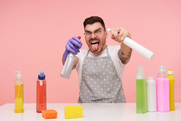 Retrato engraçado de um jovem homem de cabelos castanhos de óculos vestido com avental e camiseta branca brincando com detergentes e fazendo caretas enquanto está sentado no rosa com frascos coloridos