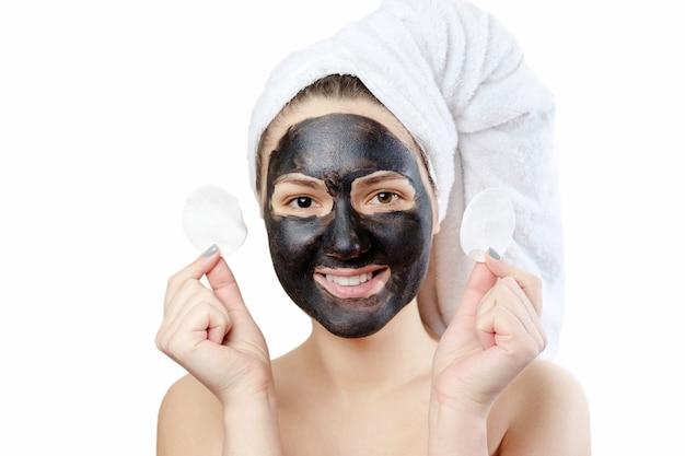 Retrato engraçado do close-up, mulher bonita com máscara facial preta em fundo branco, menina com uma toalha branca na cabeça, sorriso satisfeito e feliz, segura nas mãos as almofadas de algodão para remover a maquiagem