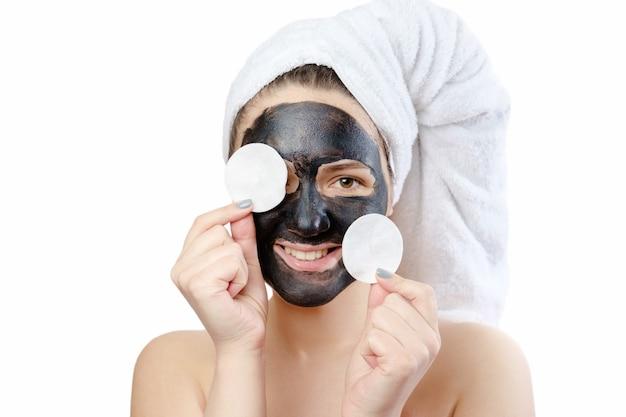 Retrato engraçado em close-up de mulher bonita com máscara facial preta em fundo branco