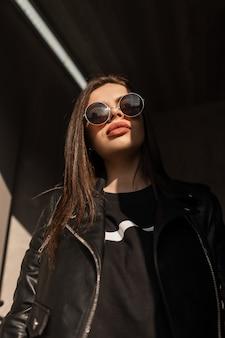 Retrato ensolarado da bela mulher legal na moda com óculos de sol redondos vintage na elegante jaqueta de couro preta e moletom fica nas sombras e na luz. moda e beleza urbana