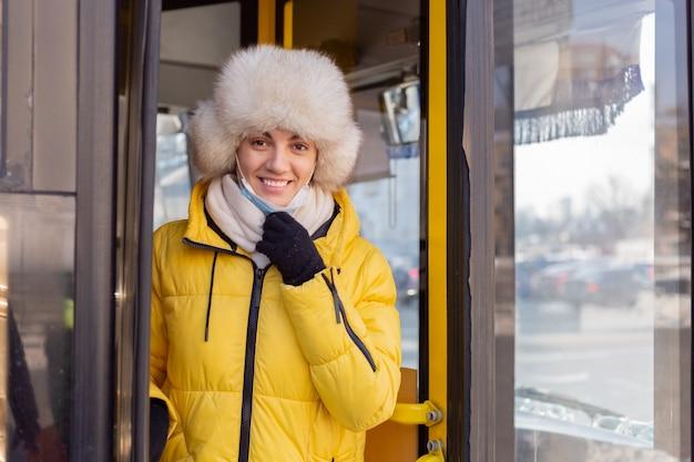 Retrato ensolarado de uma jovem com roupas quentes, feliz e sorridente, sai do ônibus e tira a máscara protetora