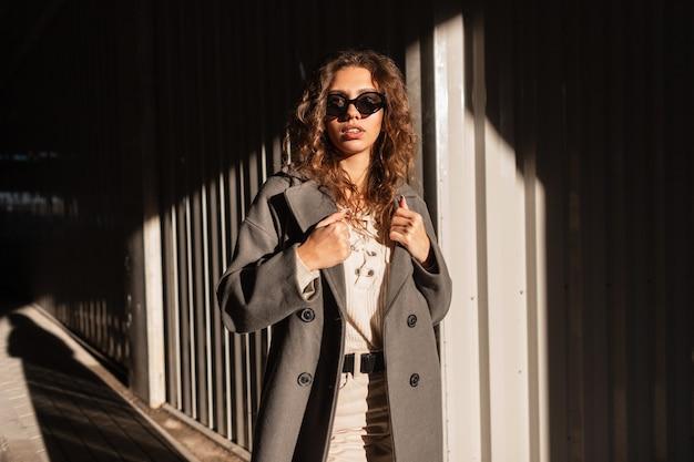 Retrato ensolarado de uma linda garota de cabelos cacheados na moda com óculos de sol em um casaco e camisola casual elegante caminha na cidade à luz do sol e à sombra. estilo urbano feminino