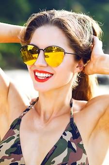 Retrato ensolarado de uma linda mulher na luz solar, cores brilhantes e clima da moda, corpo forte de fitness, férias de verão.
