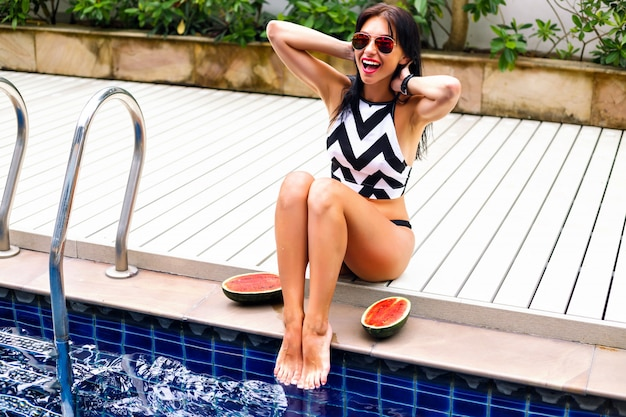 Retrato ensolarado de verão de mulher morena feliz descansando perto da piscina, aproveitando o clima quente, usando biquíni e óculos escuros, tempo de férias.