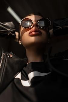 Retrato ensolarado elegante de mulher bonita hippie na moda com lábios de beleza natural em roupas pretas da moda com óculos de sol redondos vintage na luz do sol e na sombra